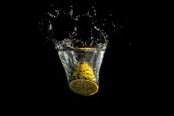 Halved fresh lemon splashing into clean water