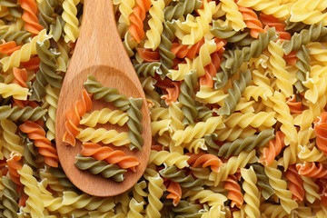 Raw colorful fusilli pasta in a wooden spoon