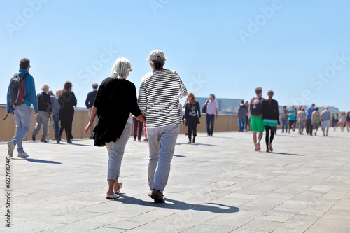 canvas print picture People walking along the seashore.