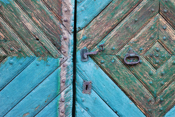 Old door painted peeling turquoise paint