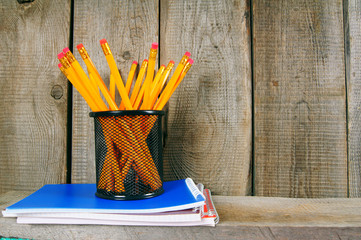 Pencils and writing-books on a wooden shelf.