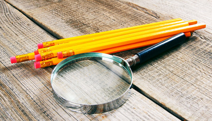 Magnifier and pencils. On wooden background.