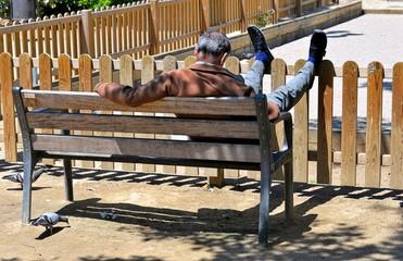 Älterer Mann schläft auf der Parkbankank