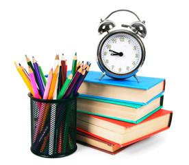 Books, an alarm clock and school tools.