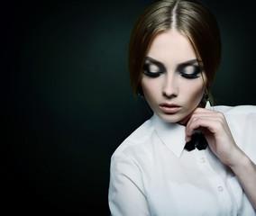 Fashion girl over black. Beautiful young woman posing at studio
