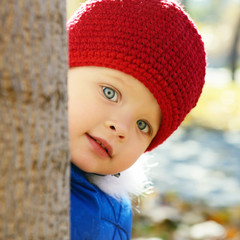 Cute playful little girl  look out of tree in autumn park.