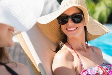 Women wearing hats by swimming pool