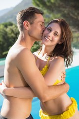 Young man kissing woman by swimming pool
