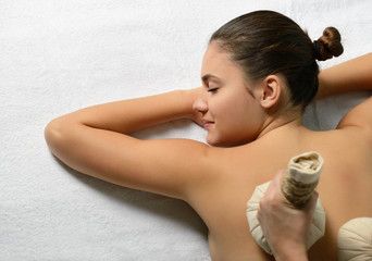 portrait of young beautiful woman in spa salon gets massage with