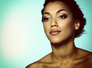 Young mulatto fresh woman with beautiful makeup, isolated on blu