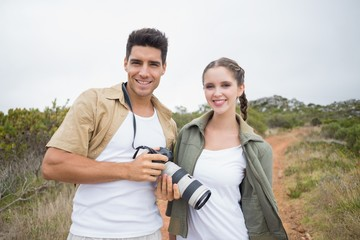 Hiking couple holding camera on mountain terrain