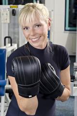 Reife Frau im Fitness Studio bei Box-Übungen