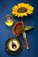 Sunflower oil and flowers on blue background