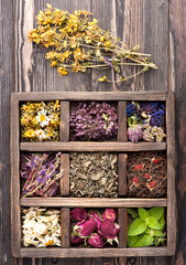 Dried Herbs and flowers in vintage box on wooden background.