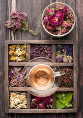 Dried Herbs and flowers in vintage box and herbal tea