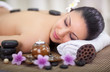 beautiful woman in spa salon with hot stones in back