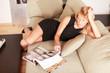 attraktive Frau auf dem Sofa Zeitschrift lesen