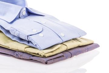 folded brand new shirts on white
