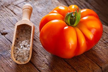 Reife Fleischtomate und Salz in Gewürzschaufel