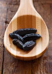 Dunkle aromatische Tonkabohnen auf einem Holzlöffel