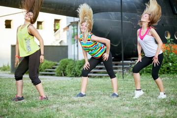 women dancing zumba, modern group choreography outdoor