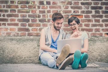 couple of friends young  man and woman using laptop