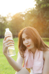 Woman Sitting and holding a bottle of water.