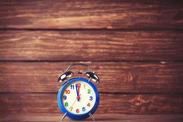 Retro alarm clock on wooden background