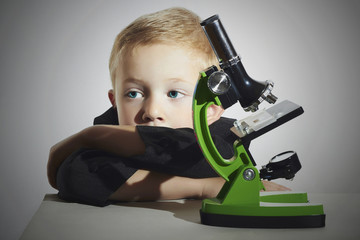 little boy don't want to study.sad child.microscope.Education