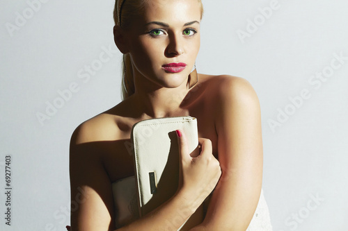 Beautiful blond woman.Fashion Stylish girl with white clutch