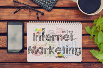 Notebook with text inside Internet Marketing on table