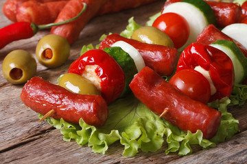 grilled sausages with tomato, olives, chili, onions on skewers