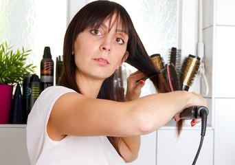 Junge Frau beim Haare glätten