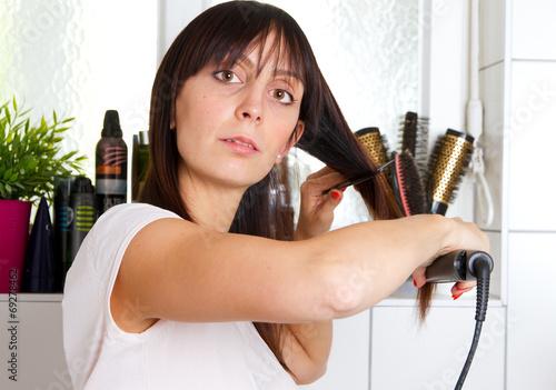 canvas print picture Junge Frau beim Haare glätten