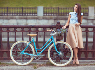 Young elegantly dressed woman with bicycle, summer and lifestyle
