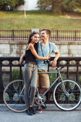 Happy couple - man and woman with bike in the park outdoor