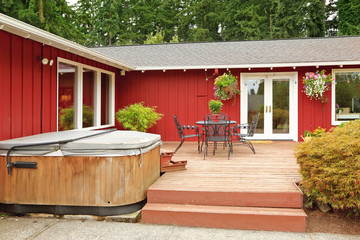 Bright red house with walkout deck and patio area