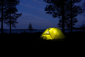 tent glowing in the darkness in the forest with lake