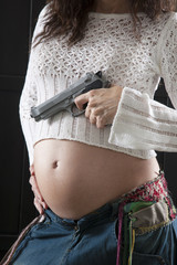 gun in pregnant woman hand