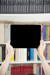 hands showing blank screen tablet over library