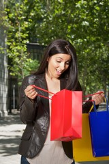 happy woman with shopping bags at street in Madrid city Spain.