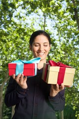 woman with two gift boxes over green trees.