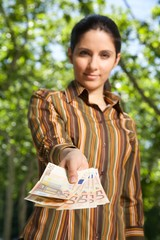 businesswoman offering you a banknote Euros in her hand.