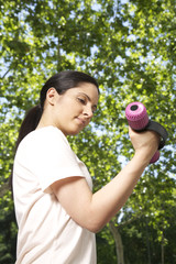 pretty brunette woman lifting pink dumbbell