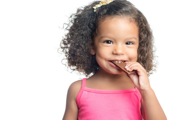 Little girl with an afro hairstyle eating a chocolate cookie