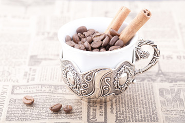 White coffee cup on newspaper with cinnamon