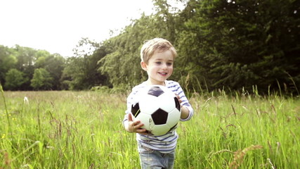 Little Boy Running With Soccer Ball
