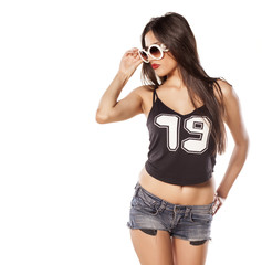serious girl in short jeans and sunglasses on white background