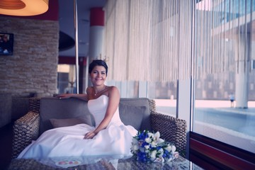 Beautiful bride sitting at an indoor cafe