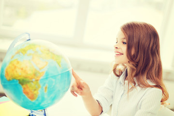 smiling student girl with globe at school